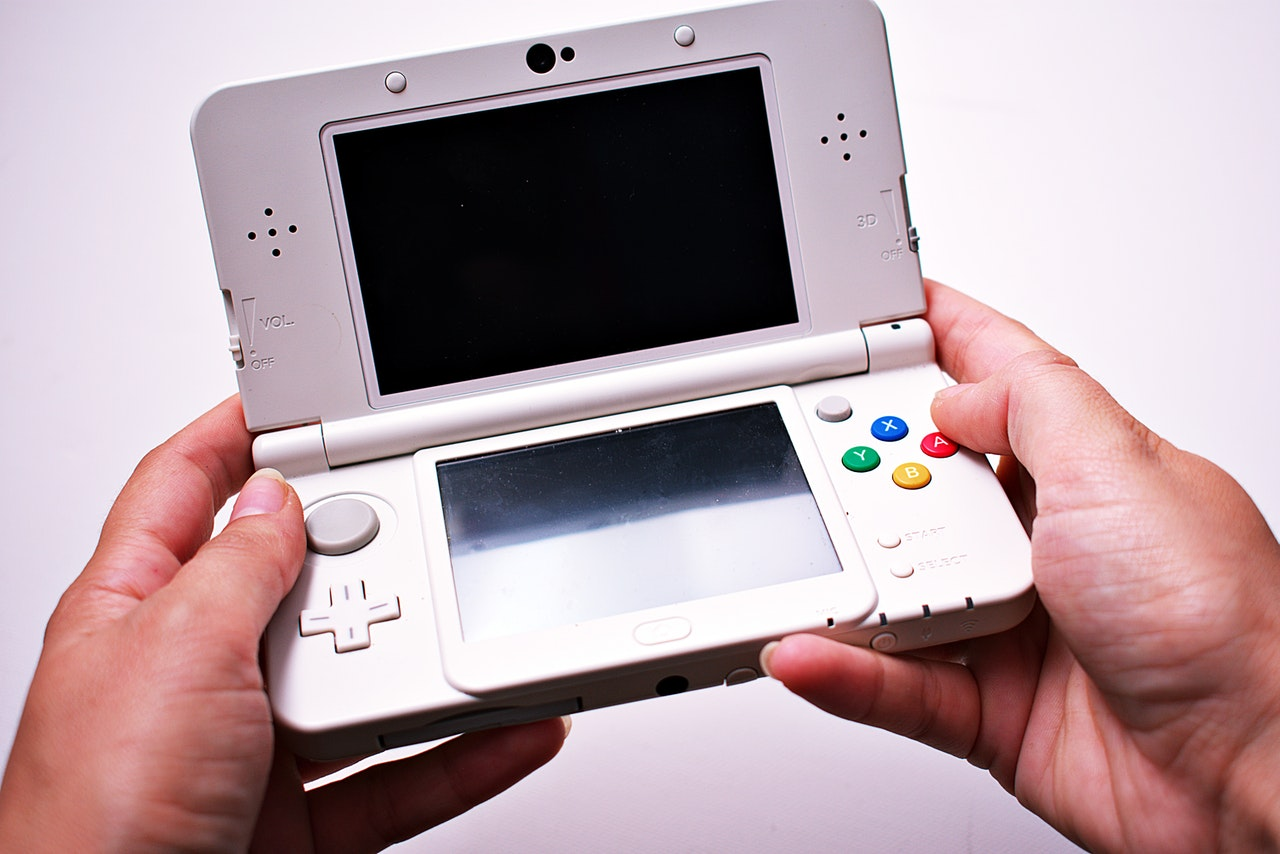 person-holding-portable-game-console